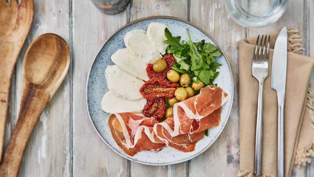 LowCarb High Fat Meal. Italian style Antipasti selection. Parma Ham, Mozarrella, salad leaves, green olives. Salad servers to one side. on wooden table.