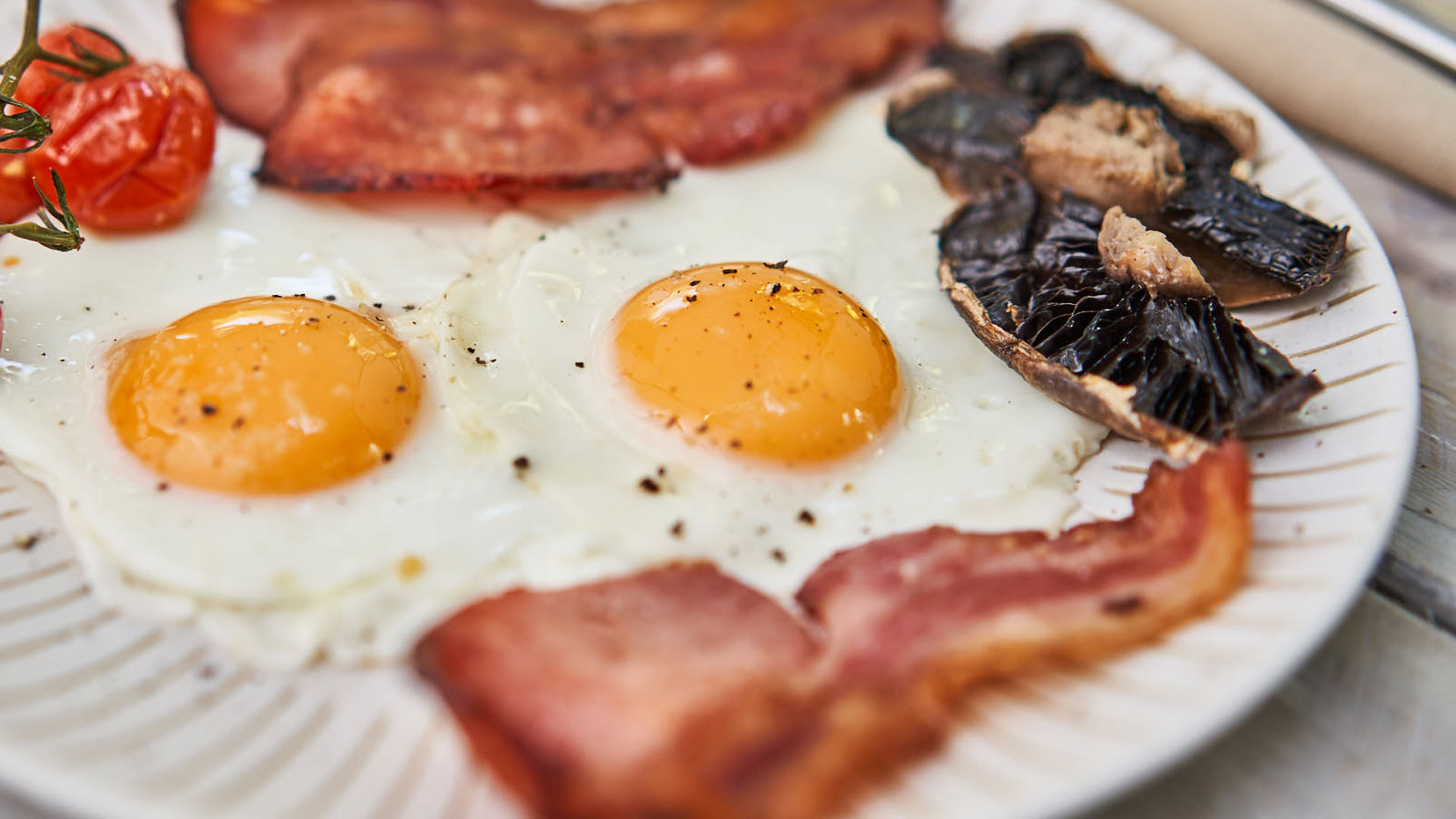 Two Fried eggs, bacon, mushroom on a plate, close up
