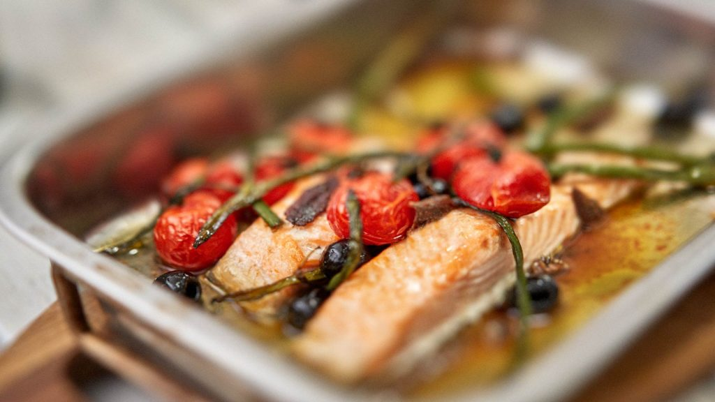 Low Carb High Fat Meal. Salmon, Tomato, beans and olives drenched in olive oil. All presented in a steel cooking pan or tray. Vegatbles are wilting with oven heat. Close up view.