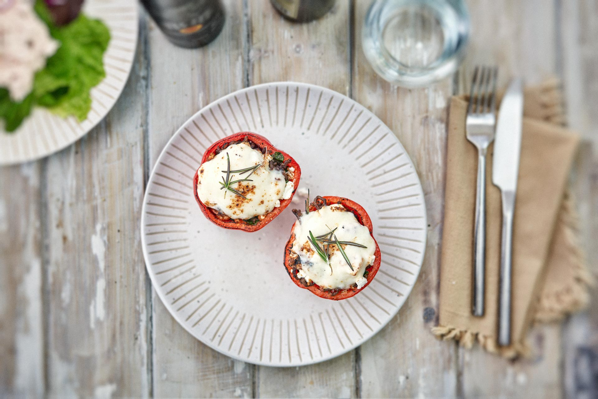 Stuffed Red Peppers. Low Carb High Fat Meal. Melted Mozzarella cheese on mincemeat, inside a cooked pepper. on a cream plate, on a wooden table.
