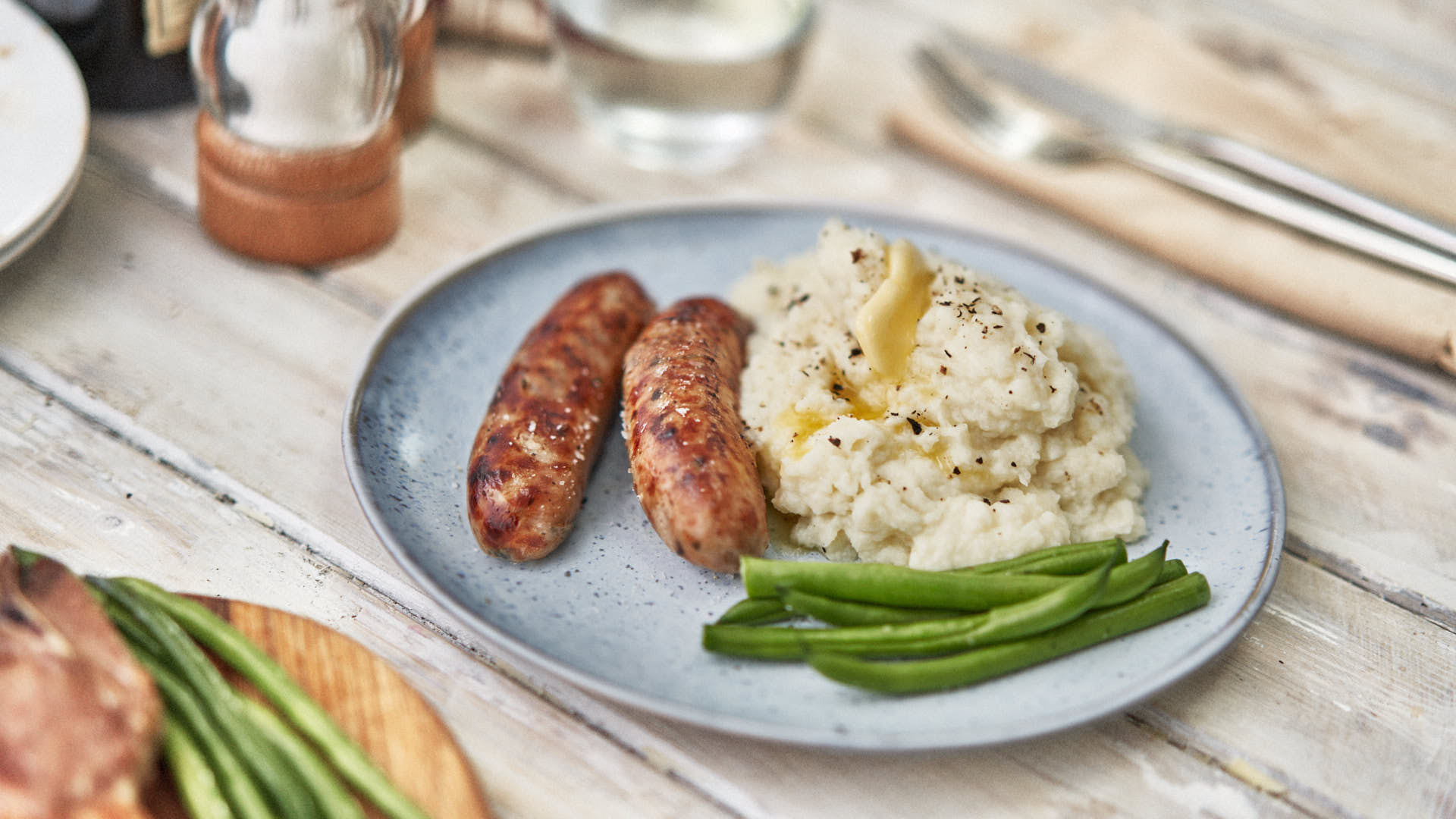 Low Carb High Fat Meal. Two pork sausages and Cauliflower Mash with green beans. On a light blue plate.On Wooden Table. Cutlery and condiments out of focus in background.