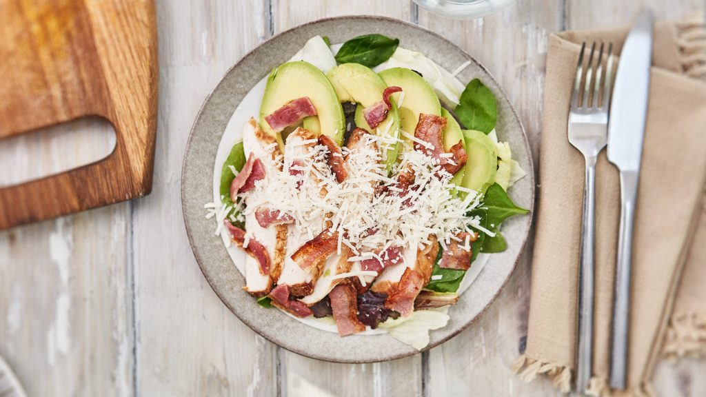 Low Carb High Fat Salad Meal. Avocado, Grilled Chicken, Bacon, with grated Parmesan cheese. Yolk running onto plate. On plate, on wooden table.