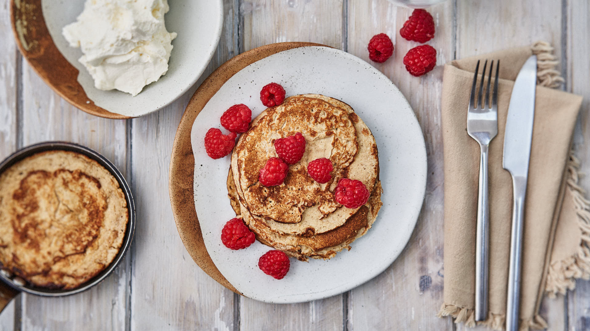 Low Carb High Fat Breakfast Meal. Pancakes. Bowl of whipped double cream. 14 raspberries scattered over pancakes. On wooden table. Cutlery visible to side. Small frying pan to left side.