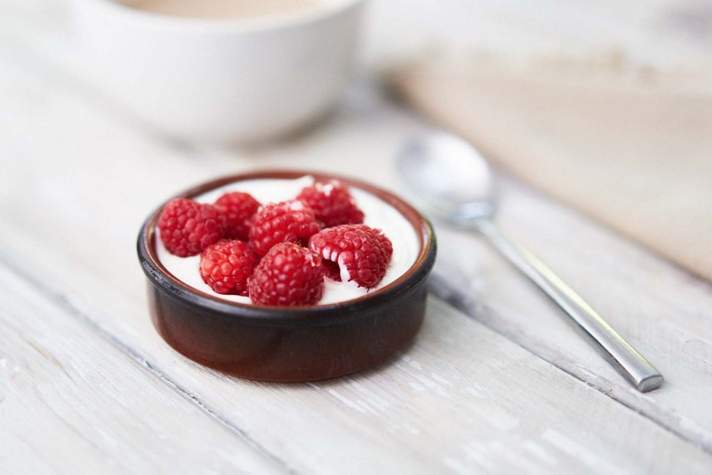a bowl of fresh raspberries and yoghurt. a low carb breakfast.