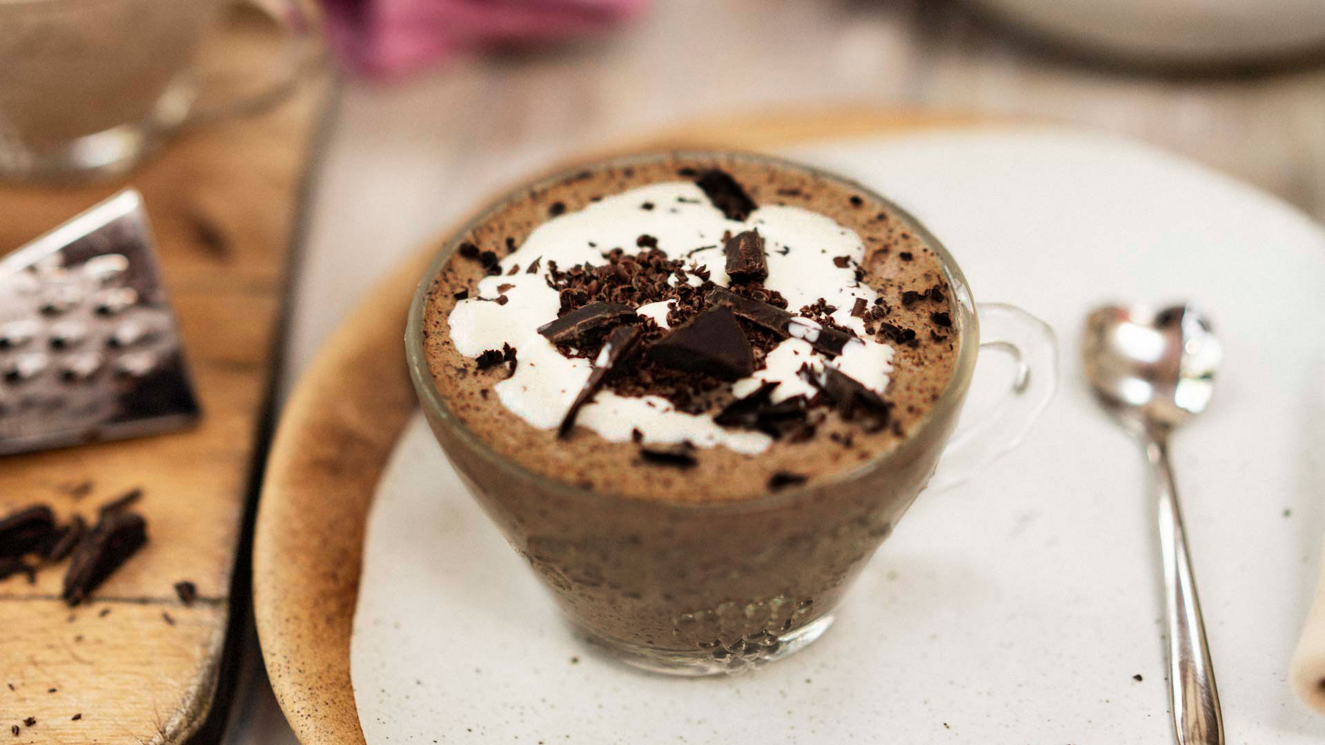 A chocolate mousse. A glass full of dessert. cream and grated chocolate on the top